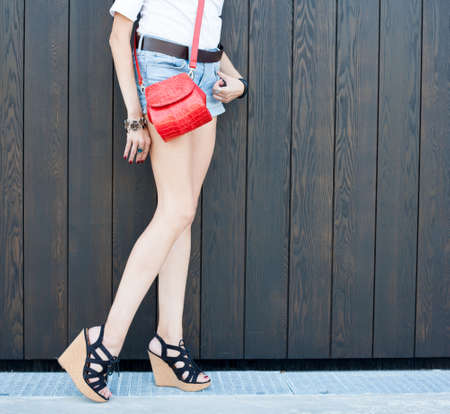 fashion leggy girl in a beautiful high-heeled shoes in short denim shorts summer posing near the dark wall. close-up