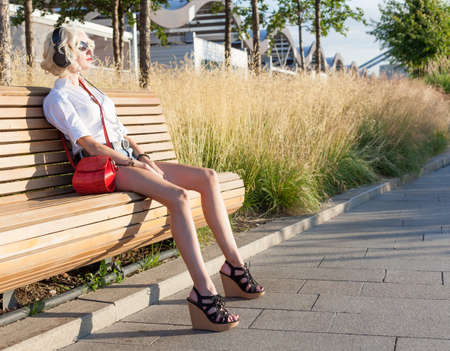 leggy girl: Fashion leggy girl in a beautiful high-heeled shoes in short denim shorts summer posing near the dark wall. Close-up