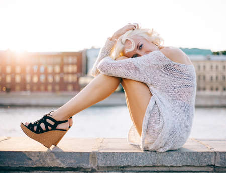Fashion leggy girl in a beautiful high-heeled shoes sitting on the waterfront at summer sunset