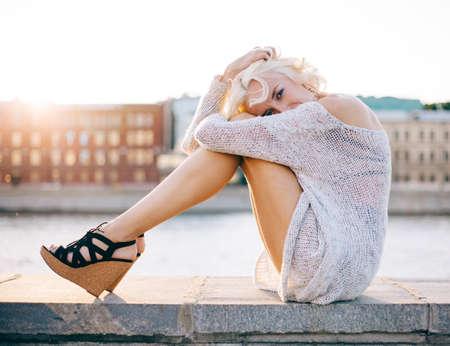 piernas con tacones: Forme a la muchacha de piernas largas en unos hermosos zapatos de tacón alto sentado en la orilla del mar al atardecer de verano