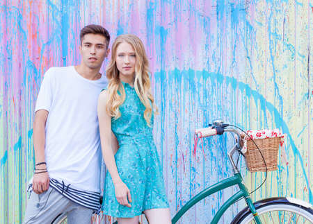 blonde hispanic: Young happy hipster couple in love meet each other and dating whis vintage bicycle. Pretty blonde caucasian woman with her hispanic boyfriend posing outdoor in summer Stock Photo