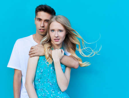 interracial love: Interracial young couple in love outdoor. Stunning sensual outdoor portrait of young stylish fashion couple posing in summer. Guyhugging girl from behind. Hispanic man, Caucasian girl. Bright blue green
