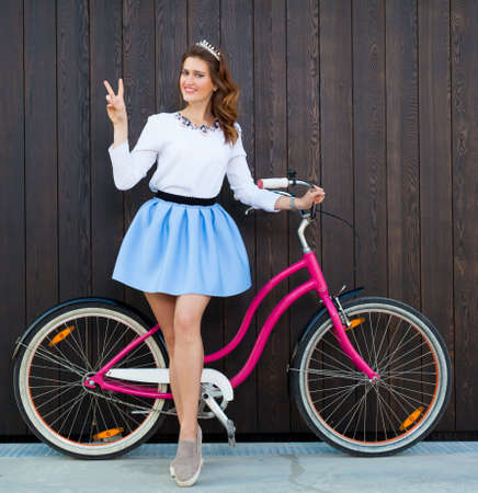 pink bike: Trendy Fashionable Girl with Vintage Pink Bike on Black Wooden Background. Toned Photo. Modern Youth Lifestyle Concept. Stock Photo