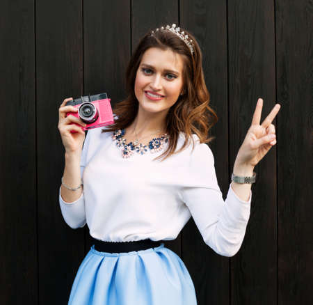 gir: Beautiful fashionable gir with pink vintage camera, a blue short skirt posing near the wooden wall of a warm summer evening