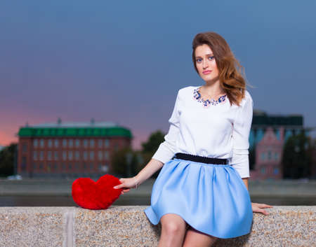 fashionable girl: Beautiful fashionable Girl with red heart in the park in warm summer evening sitting on a stone bank of the river Stock Photo