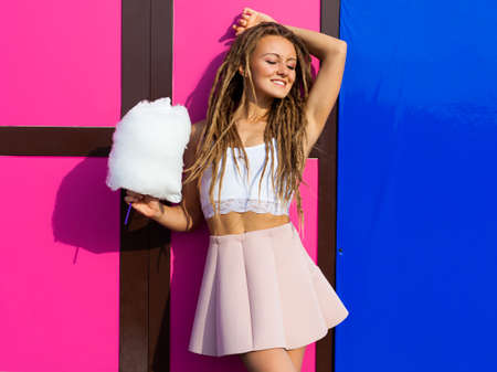 cotton candy: Beautiful young woman in a pink skirt posing near wall with bright cotton candy summer warm evening