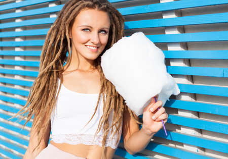 dreads: Beautiful young woman with dreads posing near blue plank wall with cotton candy summer warm evening