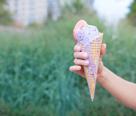 icecream cone: Beautiful womans hand holding a colorful ice-cream cone. Close up. Outdoor. Summer time Stock Photo