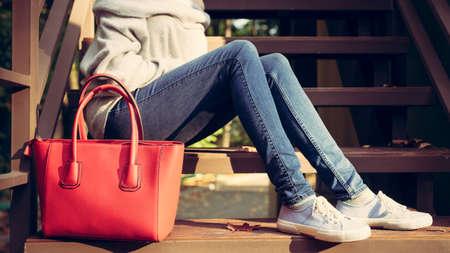 escarpines: Chica sentada en las escaleras con un rojo grande bolsos súper de moda en un jeans suéter y zapatillas de deporte en una cálida noche de verano. Colores cálidos Foto de archivo