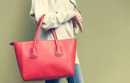 Mooie jonge vrouw poseren, jeans, rode grote handtas en trui