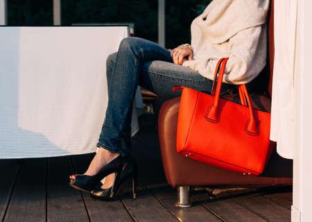 セーターに大きな赤い超おしゃれなバッグで夏のカフェのソファーに座っている女の子のジーンズとスニーカーは暖かい夏の夜に。温かみのある色