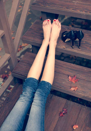 nude girl sitting: very beautiful long legs, a girl is resting after a long walk sitting on the steps a warm autumn evening Stock Photo