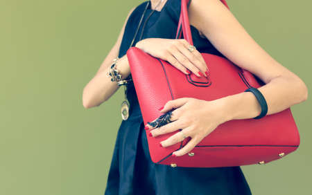 Fashionable beautiful big red handbag on a shoulder of the girl in a black dress trendy. Warm colors Banque d'images