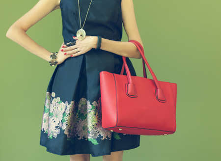 Fashionable beautiful big red handbag on the arm of the girl in a fashionable black dress, posing near the wall on a warm summer night