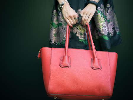 ファッショナブルな美しい大きな赤いハンドバッグ暖かい夏の夜に壁に近いポーズ ファッショナブルな黒のドレスで女の子の腕に。暖かい色 写真素材