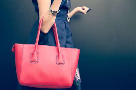 Divatos szép nagy piros táska a karját a lány egy divatos fekete ruhában pózol a fal mellett egy meleg nyári éjszakán. Meleg szín