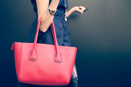 Fashionable beautiful big red handbag on the arm of the girl in a fashionable black dress, posing near the wall on a warm summer night. Warm color. Stock Photo