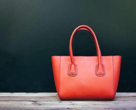 Moda grande hermoso bolso rojo de pie en un piso de madera en la pared de fondo negro