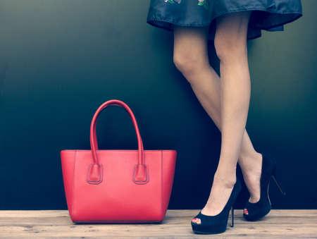 moda ropa: Forme a la muchacha de piernas largas en unos hermosos zapatos de tacón alto en vestido de mezclilla corto verano posando cerca de la pared oscura. Acercamiento. Color cálido