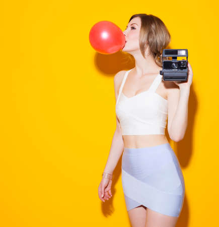 Fashionable modern posing in colorful top and skirt inflates the red bubble from chewing gum on yellow background in the studio. Fashion Beauty Girl. Gorgeous Woman Portrait. Stylish Haircut and Makeup. Hairstyle. Make up. Sexy Glamour Girl on Yellow back