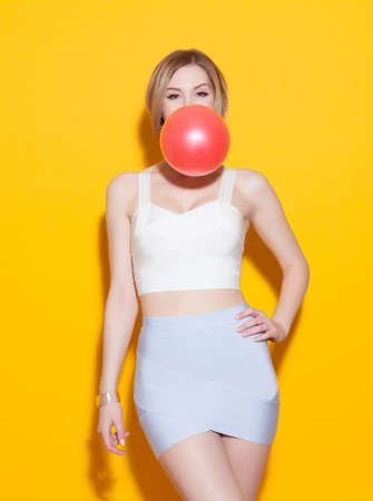 Fashionable modern posing in colorful top and skirt with inflates the bubble from chewing gum at yellow background in the studio. Fashion Beauty Girl. Gorgeous Woman Portrait. Stylish Haircut and Makeup. Hairstyle. Make up. Sexy Glamour Girl on Yellow bac