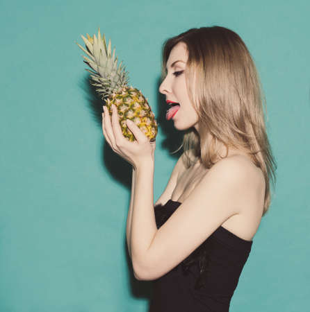 girl holding hands pineapple and reaches for his tongue in a black dress on a green background in the studio Stock Photo