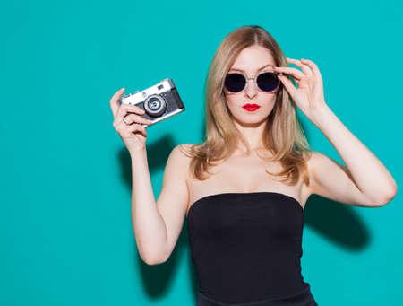 美しいファッショナブルな女の子ポーズと黒のドレスでスタジオで背景が緑色のサングラス ビンテージ カメラを保持しています。ゴージャスな女性 写真素材
