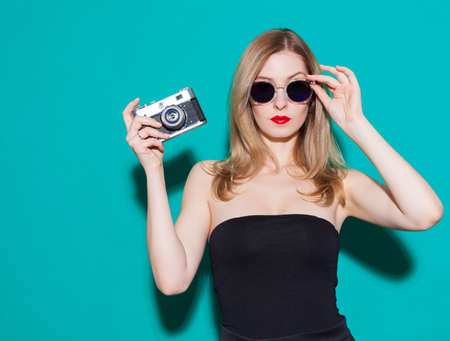 Beautiful fashionable girl posing and holding a vintage camera in black dress and sunglasses on the green background in the studio. Gorgeous Woman Portrait. Stylish Haircut and Makeup. Sexy Glamour Girl.