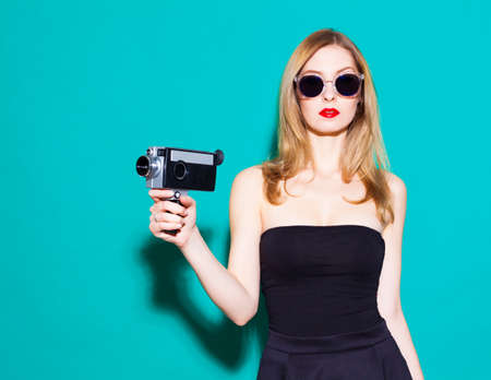 Beautiful fashionable girl posing and holding a vintage movie camera in black dress and sunglasses on the green background in the studio. Gorgeous Woman Portrait. Stylish Haircut and Makeup. Hairstyle. Sexy Glamour Girl.