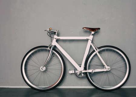 fixed: Engranaje fijo hermosa bicicleta de cosecha está próxima a gris de fondo