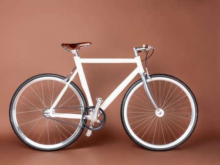 clavados: Fijo Gear hermosa bicicleta de la vendimia se encuentra en un fondo marrón Foto de archivo