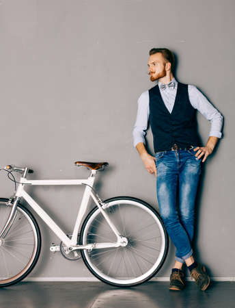metrosexual: A young man with mustache and beard is near fashionable modern fixgear bicycle. Jeans and shirt, the bow tie hipster style. Toned color