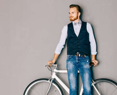 metrosexual: A young man with mustache and beard is near fashionable modern fixgear bicycle. Jeans and shirt, vest and the bow tie hipster style. Grey background. Toned color