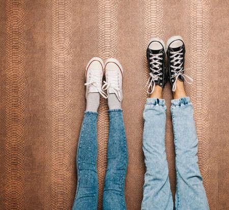 piernas: piernas de la pareja de moda joven en pantalones vaqueros y zapatillas de deporte de los pies encima de la pared. De cerca Foto de archivo