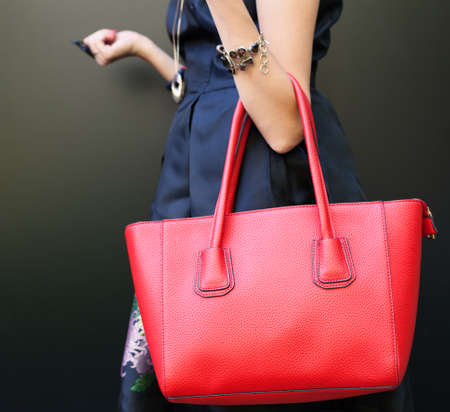 Modieuze mooie grote rode handtas op de arm van het meisje in een modieuze zwarte jurk, die zich voordeed in de buurt van de muur op een warme zomeravond. Warme kleur. Detailopname