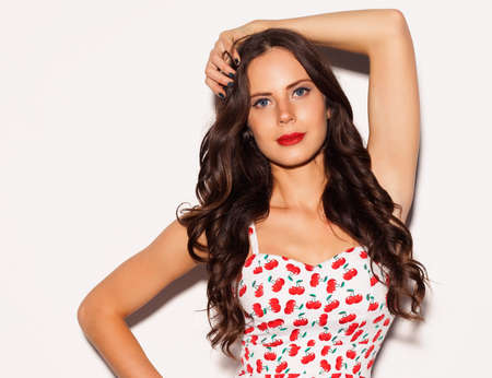 Schöne gleichaltrige Mädchen mit langen Haaren und blauen Augen in hellen Sommer-kurzes Kleid nex auf weißem Hintergrund aufwirft. Nahansicht. Innen- Standard-Bild