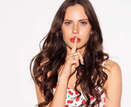 흰색 배경 위에 그녀의 입술에 손가락을 가리키는 아름 다운 젊은 여자의 초상화. 개념 침묵 비밀. 실내.
