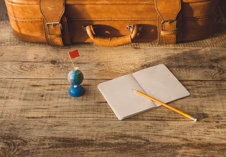 attainment: Suitcase, nootbook, pencil, flag on wooden plancs. Aim, attainment, target, tourism, travel.