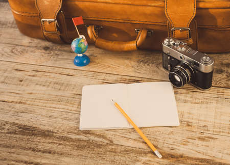 attainment: Suitcase, nootbook, pencil, flag, vintage camera on wooden plancs. Aim, attainment, target, tourism, travel. At dawn. Hipster style. Top view with copy space. Free space for text.