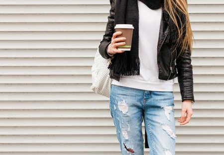 コーヒーとバックパック通りにポーズをとって髪の長い美しい金髪の少女の肖像画。屋外、温かみのある色です。クローズ アップ。 写真素材