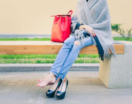 cansancio: Chica en vaqueros se quitó los zapatos de tacón alto de moda está descansando sentado cálida noche de verano en el banco en la ciudad europea. Fiesta. Compras. Cansancio.