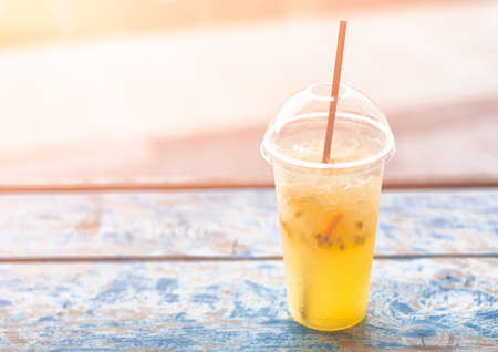 Refreshing cold drink with fresh lime, passionfruit and ice. On wooden planks. Background. Freshment. Summertime. Stock Photo