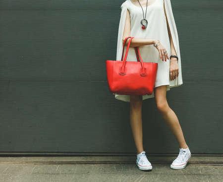 ファッショナブルな美しい大きな赤いハンドバッグ暖かい夏の夜に壁に近いポーズ ファッショナブルな白ドレスとスニーカー、女の子の腕に。暖か
