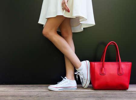 美しいファッショナブルな大きな赤いハンドバッグ ホワイト ショート ドレスと白いスニーカーで脚の長い女性の横に立っています。体の一部。
