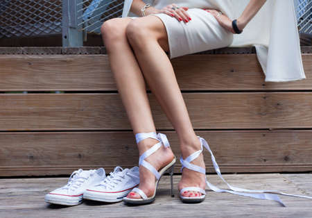 stilleto: Ribbon Tie Stilleto shoe and sneakers. Fashionable woman with long beautiful legs sitting on a wooden board and disguises footwear, Part of body.