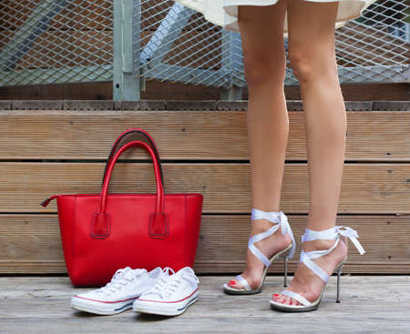 stilleto: Ribbon Tie Stilleto shoe, sneakers and fashionable big red handbag. Fashionable woman with long beautiful legs standing on a wooden background. Part of body.