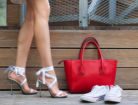 stilleto: White Ribbon Tie Stilleto shoe, sneakers and fashionable big red handbag. Fashionable woman with long beautiful legs standing on a wooden background. Part of body. Stock Photo