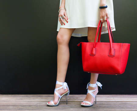 stilleto: Fashionable woman with long beautiful legs in Ribbon Tie Stilleto shoes standing on the black background. Girl holding a large red handbag.