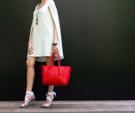 stilleto: Fashionable woman with long beautiful legs in Ribbon Tie Stilleto shoes standing on the black background. Girl holding a large red handbag. Part of body. Fashion and Style