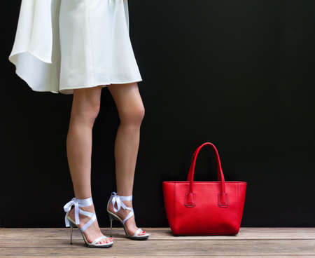 stilleto: Fashionable woman with long beautiful legs in Ribbon Tie Stilleto shoes standing on the black background. Girl stands next to large red handbag. Part of body. Fashion and Style